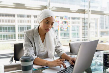 Businesswoman in hijab working on laptop at desk in a modern office