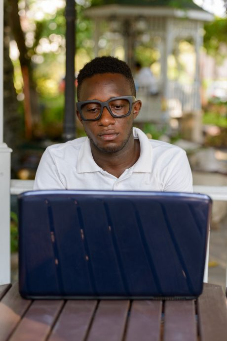 Young African man as student using laptop at the park